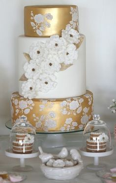 Beautiful gold and white wedding cake with cascading flowers.  I love the hand painted white flowers on the gold tiers.  Very chic!        ᘡղbᘠ