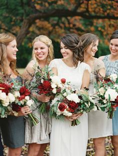 Bridesmaids in a variety of neutral and dusty blue hues. Bride's dress by Grace Loves Lace. Autumn bouquets with deep red blooms by Fern Studio Floral & Event Design, image by Landon Jacob.