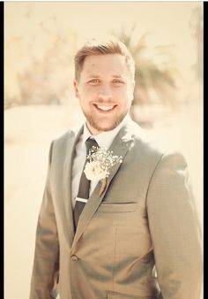 The groom looking handsome in a grey suit. His buttonhole was a bit of babies breath and rose tied together with hessian string