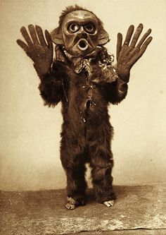 "Title: Hami–Koskimo Date Created/Published: c1914 November 13. Summary: Koskimo person wearing full-body fur garment, oversized gloves and mask of Hami (""dangerous thing"") during the numhlim ceremony."
