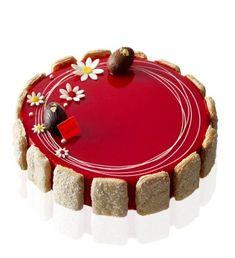 Version entremet : Charlotte aux fruits rouges faite d'un biscuit moelleux aux amandes, coulis de fruits rouges avec des fruits rouges pochés, un biscuit cuiller, une mousse à la pulpe de framboise, recouverte de glacage et décorée d'oeufs en chocolat