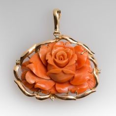 This beautiful vintage enhancer pendant features a large pink coral hand carved into a blossoming rose. The coral is set in a yellow gold basket and features an enhancer bale and 4 diamonds set around the perimeter. The pendant measures a bit shy of 1 Coral Art, Coral And Gold, Gold Jewelry Simple, Coral Jewelry, Le Jade, Coral Design, Diy Design, Book Jewelry, Women's Jewelry