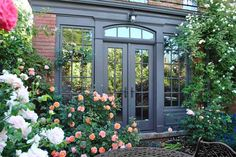 French doors invite views of the garden inside, while the painted trim outside echoes the purple- and blue-flowering perennials that wind through the garden.