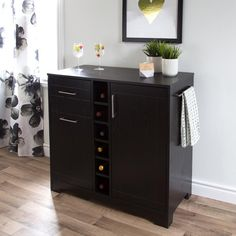 Let this multi-functional bar cabinet inspire you! It's perfect for mixing a cocktail that appeals to you or indulging your passion for great vintages. The specialized storage spaces, designed specifically for wine and liquor bottles, along with the handy drawer (ideal for accessories) and the glass holders mean everything you need to entertain your friends in style is right there at your fingertips. It also features a spill-proof top and towel holder, so no worries if you pour too much…