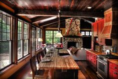 rustic kitchen ideas.  I like the fireplace, the windows, the island/table, even the shabby red cabinets.  Hmmm..c