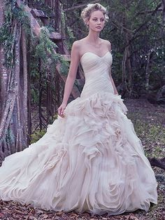 Maggie Sottero - PENNY, An asymmetrically pleated bodice provides a slim fit through the hips before meeting the grand, swirling tulle and Vincenza organza skirt of this mermaid wedding gown. Finished with a soft scoop neckline and covered buttons over zipper and inner elastic closure.