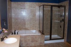 Glass shower/whirlpool tub combination with bold blue walls and excellent tile work