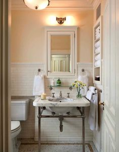 Beautiful bathroom with mosaic marble hex tiles floor with gold decorative inset border tiles, 2 leg marble washstand, pencil rail with subway tiles backsplash, vintage glass shelf, white inset medicine cabinet and built-in shelves. Source: John B Murray Architect