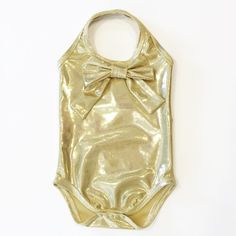"The Golden Hill Design ""Gold Digger"" our halter bodysuit in Shinny Gold with an adorable bow attached. And it is POOL SAFE! Our bodysuits come with snaps that makes for easy diaper changes! Perfect for soggy swim-diapers!"