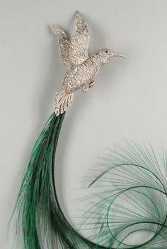 A diamond 'colibri' bird of paradise hatpin, by Van Cleef & Arpels, circa 1921, FOOTNOTES In the 1920s Van Cleef & Arpels made a series of brooches and hat pins in the form of exotic birds set with rose-cut diamonds in platinum, some with detachable natural feathers, c.f. Editions Paris-Musées, Van Cleef & Arpels, Paris 1992, p.154, catalogue no.237 Oiseau de Paradis clip, 1927, and no. 238 Colibri clip, 1925.