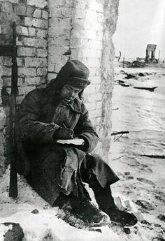 Советский солдат, сидящий в руинах Сталинграда, пишет письмо о конце сражения.Январь 1943 года.