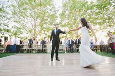 A perfectly placed dance floor for this outdoor winery wedding. Such fun seeing this glowing couple enjoying their first dance while surrounded by their family and friends! Beautiful photo captured by: Onelove Photography | Design by: So Eventful​ | Dancefloor: Encore Events Rentals​ #encoreeventsrentals #dancefloor #bistrochairs #napavalleylinen #outdoorwedding #winerywedding #happycouple #newlyweds #weddingreception #firstdance