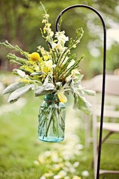 Decorating Idea: Here's a different way of using those wrought iron garden hooks. Instead of hanging a planter, wrap wire around the neck of a glass jar and form a handle. Fill with fresh cut flowers and hang on the hook for a totally unique look! from Della Creations