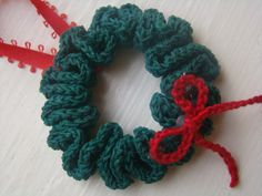 Fun Christmas Ornament! This wreath is simple and fun to crochet! Find this free crochet pattern and hundreds of others at Craftown.