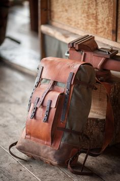 simple leather and canvas rucksack with one front pocket and four straps.