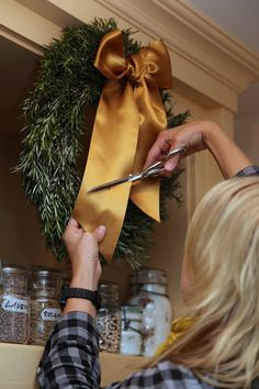 Snipping a beautiful satin ribbon on a fragrant rosemary wreath - perfect for a kitchen!