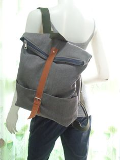 This bag is made of a gray canvas fabric. Dimensions:    Height -- 14 inches  Width -- 15.5 inches  Straps -- 21-39 inches      Care instructions: