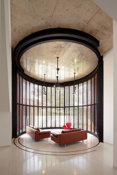 Circular sitting area partially enclosed by revolving wooden doors which can be opened to create an outdoor space in this home in Kuala Lumpur Malaysia. [1000  1500]