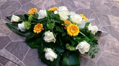 Funeral spray with white roses and yellow germinis