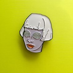 "She's hypnotizing! This girl with spiral eyes and lavender skin is our newest 1.25"" soft enamel pin and she's perfect for your collar or bag Approx 1.25"" tall Soft enamel Metal back with rubber clasp"