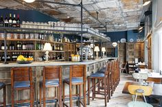 Reclaimed wood panelled walls, tin ceiling and variety of found bar stools chairs and tables by Martin Brudnizki Design Studio | Pizza East, Portobello