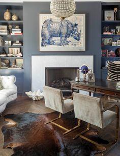 Contemporary home office, cowhide rug, rhino art, dark wood desk, gold metal and suede armchairs   Robert Elliott Custom Homes