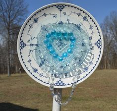 Darling piece of yard art in blues.  Large plate is Royal China with Delft underlay, with clear blue scalloped plate and a clear heart dish to top it off.  Blue glass stones and chandelier beads for accents.    Blue Heart Yard Art
