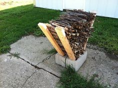Easy peasy kindling rack: 2 cinder blocks + 4 chunks of wood you most likely will have in your scrap pile. Prop the pieces of wood in the 4 outer holes of the cinder block so that they fall away at an angle. Fill the void with kindling or firewood to dry.