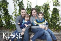 Ivy and white picket fence backdrop for this family portrait.