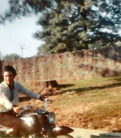 Elvis riding a motorcycle up the drive at Graceland, Memphis, June 1969