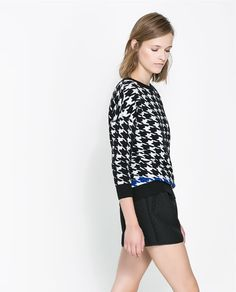 Black and white  herringbone sweater with cobalt accent on bottom