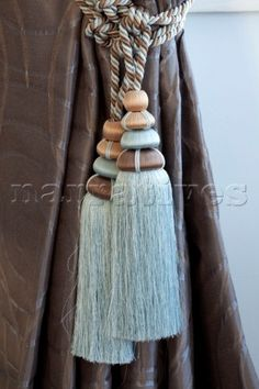 Turquoise and brown tassels tie back curtains in Hendon home London UK