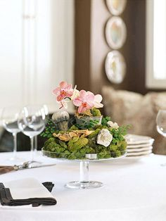 Stack of moss covered stones & flower accents, set atop a cake stand, adding height for additional table space for guest favors.