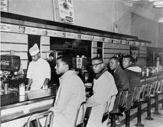 Four college students sit in seats designated for white people at the racially segregated Woolworth lunch counter in Greensboro, NC, in 1960.