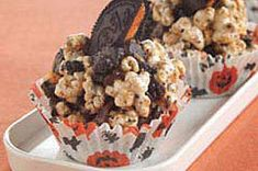 Cookies 'N Cream Jack-o'-Lantern Popcorn Balls - Kids love these colorful popcorn balls studded with chopped chocolate sandwich cookies and raisins and decorated to resemble jack-o'-lanterns.