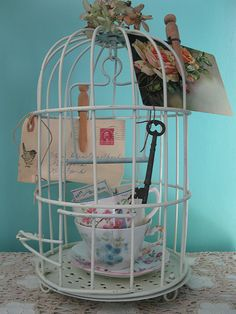 Cups and postacards in a bird cage