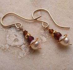 Pearl garnet earrings. White pearls dangle below red garnet and amber brown tourmaline gemstones with beads and gold pyrite beads to create these simple earthy gemstone earrings. The earrings hang at just about 1 from the top of the earwire to the bottom of the pearl.  Pearls are said to stimulates spiritual transformation and promote prosperity and success. Pearl is the ayurvedic and modern birthstone for June.  Garnet is said to bring self esteem and business success. Garnet is the…