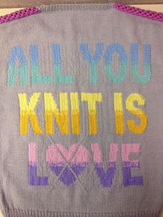 "All you knit is love…do you agree? If so, this sweater is the perfect way to express that sentiment! This design incorporates everything you love about knitting, from colorwork, to cables, and even lace! With the featured phrase in bold block letters on the back in a rainbow gradation of colors, this sweater makes quite the statement while having a soft, pretty, feminine look. The front features mini intarsia hearts with crossing cables to give an argyle look, while this ""heart-gyle"" motif…"