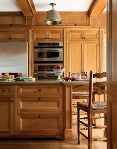 Stainless-steel appliances gleam against the burnished wood. Sub-Zero refrigerator, General Electric microwave, and wall-mounted oven with Trivection Technology. Cabinet hardware is by Ball & Ball.   - HouseBeautiful.com
