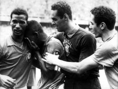 Brazil's Pele (second l) cries on the shoulder of Didi (l) as teammates Gilmar (second r) and Orlando (r) congratulate him on his fantastic performance in the final