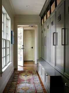 Gorgeous entryway mudroom with custom dark green gray locker cabinets with handle bar pulls, a built-in storage bench with drawers below, open shelving with cubbies above, plenty of natural light and a vintage runner rug to complete the cozy, classic and colorful feel.