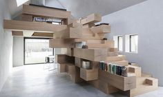 Inside this cleverly-converted barn is a stack of timber beams that serve as a shelving system, seating area, library and a staircase all in one. The renovated barn is tucked away in West Flanders, Belgium, where Studio Farris Architects converted the old structure into a contemporary office that marries modern design with rural architecture.