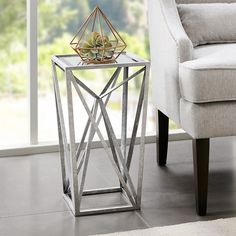 This accent table brings elegance to any room with its modern angular shape. Featuring a faux silver leaf finish and beveled mirror tabletop, this end table is sure to shine in the living room. No assembly required.