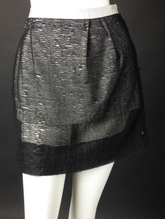 2010 Collection. Awesome little mini skirt in black silk organza entirely covered in tiny tucks. The skirt has a white waistband with the skirt falling in two released darts on either side of the cent
