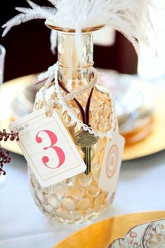 Table number with vase filled with marbles.  For our wedding, put the white or green marbles with either a white or clover colored feather.