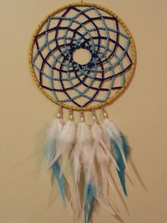 A true art form with a mix of light and dark blue beads weaved onto the web of this dreamcatcher! Large size with a 9 circle and 20 long. Made