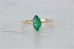 This ring features a beautiful marquise cut emerald in a classic 14k yellow gold solitaire mounting with four prong head. Its navette shape and brilliant color make a great twist on a timeless design for an engagement ring.  MAIN STONE: Genuine Emerald SIZE: Approximately 9.1 x 4.4 mm / .53 carats ERA; MARKINGS: Vintage Estate 1980's; 14K CONDITION: Good vintage condition. RING SIZE: Approximately US 7 / AU N 1/2 and sizable RING WEIGHT: 0.9 dwt / 1.4 grams RING MEASUREMEN...