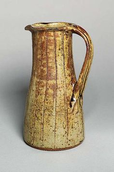 a tall Pitcher, circa 1966<br>stoneware, running green ash glaze, vertical cutting and indents to the strap-handle, impressed BL and Leach Pottery seals<br><I>Height 12 1/2in. (31.7cm)</I>