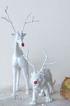 Genius! Plastic toys with twigs glued on heads as antlers, spray paint white and dab some red paid or red glitter on the nose!