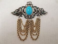 This is a very nice #Hobe' brooch. It is done in an antiqued gold toned metal, and has a large turquoise cabochon as a center piece. The metal work is intricate, and has a v... #hobe' #chains